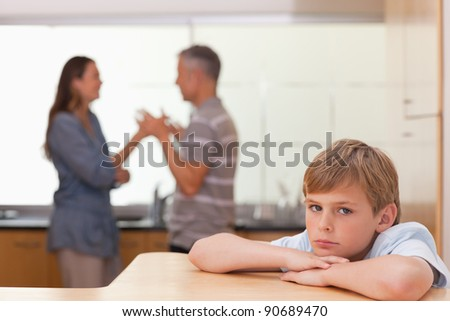 Sad boy hearing his parents having am argument in a kitchen - stock photo
