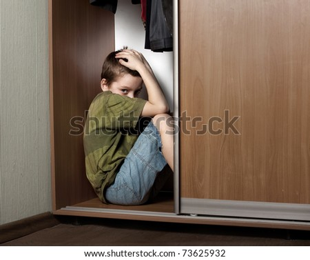 Sad boy, hiding in the closet at home