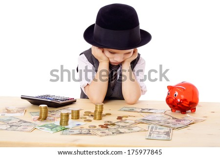 Sad boy in black hat at the table with pile of money, isolated on white - stock photo