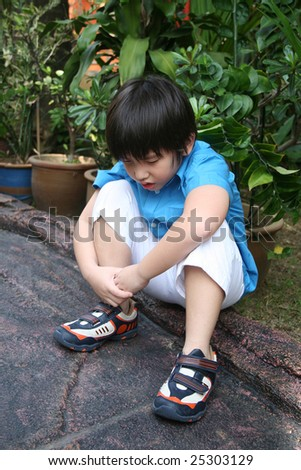 Sad boy in blue shirt sitting in the park - stock photo