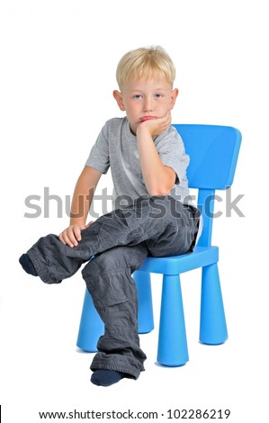 Sad boy sitting on a chair, isolated on white background - stock photo