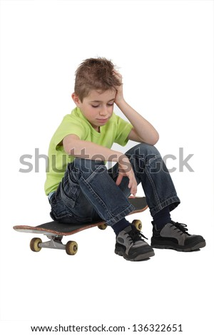 Sad boy sitting on skateboard - stock photo