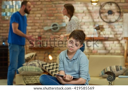 Sad boy sitting on sofa with tablet while parents shouting, arguing at background. - stock photo