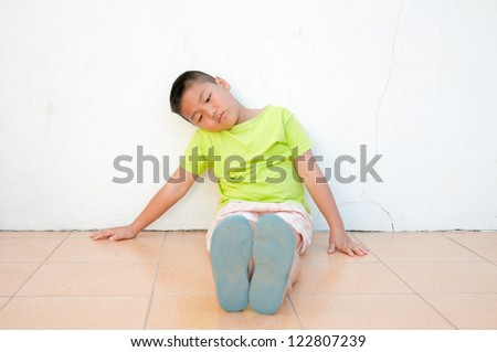 Sad boy sitting on the floor by the wall - stock photo