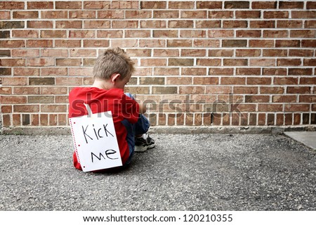 Sad boy sitting with a kick me sign on his back - stock photo