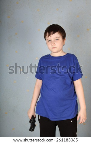 Sad boy with a joystick in hand. Boy lost in a computer game. - stock photo