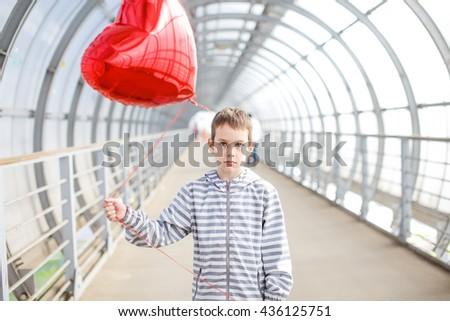 sad boy with a red heart in the hands. love-lorn. child standing with a red heart-shaped balloon. one-sided love  - stock photo