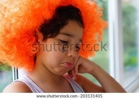 Sad boy with clown hair wig and tear on cheek - stock photo