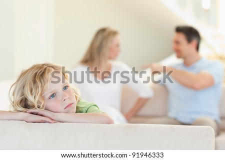 Sad boy with his fighting parents behind him - stock photo