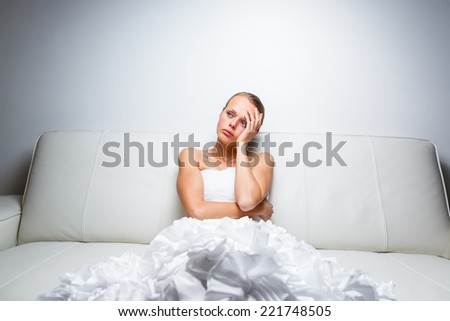 Sad bride crying, sitting on a sofa, smitten, feeling low and depressed - stock photo