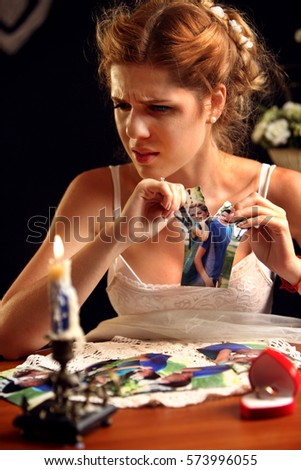 Sad bride on unhappy wedding. Woman and groom quarrel. Girl in white dress tearing family pictures. Portrait crying female. Candle and wedding ring are on table.