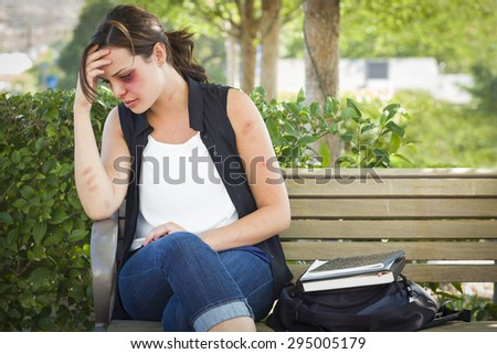 Sad Bruised and Battered Young Woman Sitting on Bench Outside at a Park. - stock photo