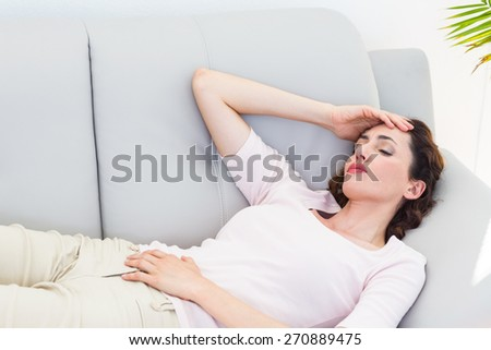 Sad brunette lying on the couch on white background