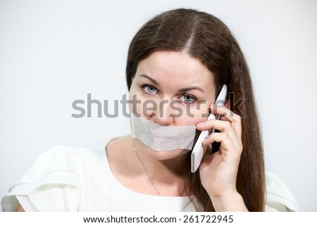 Sad brunette woman with cellphone and tape on her lips, grey background - stock photo