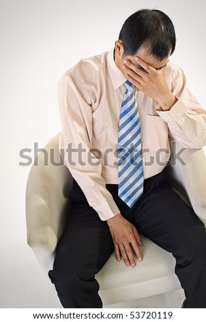 Sad business man sit on chair and cover face by hand. - stock photo
