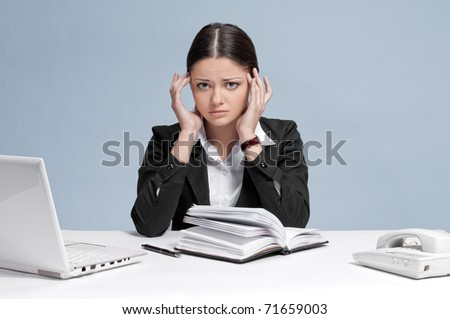 Sad business woman in office working with white table, laptop and diary personal organizer. Headache! - stock photo