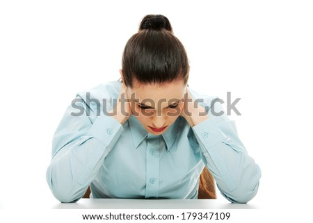 Sad business woman sitting behind the desk, isolated on white
