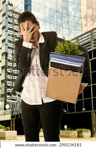 Sad Business Woman with  Cardboard Box  Fired from Job for Financial Crisis standing desperate outdoors in front of business district office buildings - stock photo