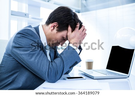 Sad businessman holding his head in his office