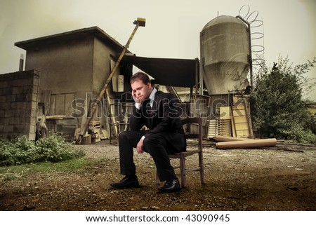 sad businessman in front of a farm - stock photo