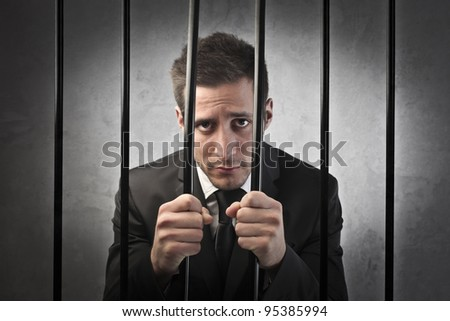 Sad businessman in prison - stock photo