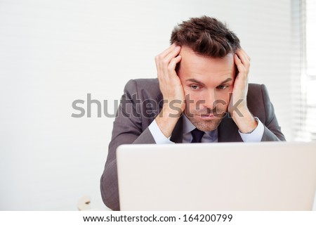 Sad businessman in the office looking at laptop - stock photo