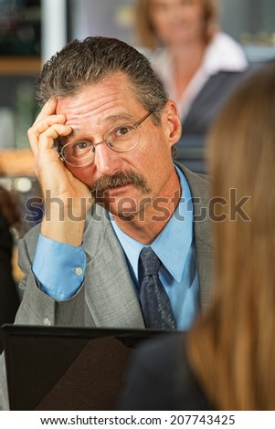 Sad businessman listening to woman in cafe - stock photo