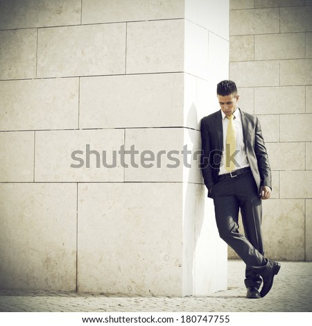 Sad businessman next to some wall looking down - stock photo