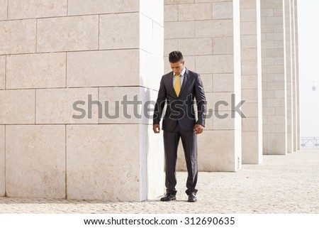 Sad businessman next to some wall looking down