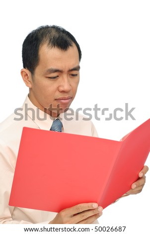 Sad businessman of Asian reviewing report on red folder with sorrowful expression on white background. - stock photo