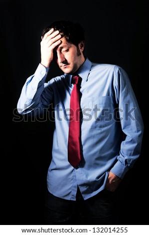 Sad businessman on dark background in low key technique light - stock photo