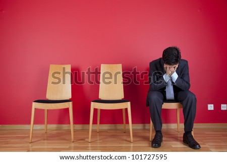 Sad businessman sited next to a red wall - stock photo