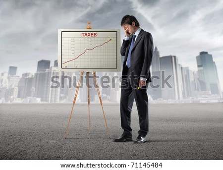 Sad businessman standing beside a graphic with cityscape on the background - stock photo