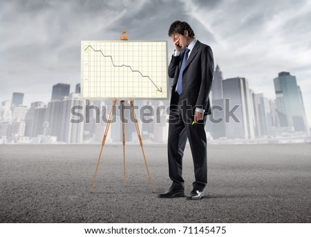 Sad businessman standing beside a graphic with negative trend