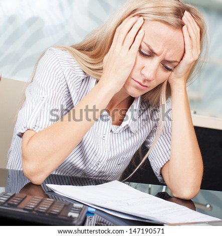 Sad businesswoman looks at the documents. Female working