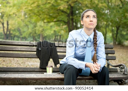 sad businesswoman  sitting on bench in park and looking up - stock photo