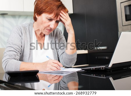 Sad businesswoman with document. Female sorting through her old receipts at home.  - stock photo