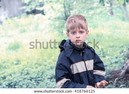 sad caucasian boy in raincoat - stock photo