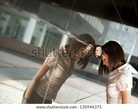 sad caucasian business woman banging her head against a wall out of office building. Reflection on wall - stock photo