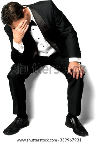 Sad Caucasian man with short black hair in a tuxedo sitting and doing facepalm - Isolated - stock photo
