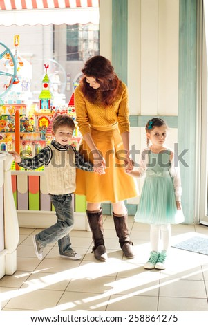 Sad child holding mother by the hand in the children's store. Son and daughter holding mother for her  hand - stock photo