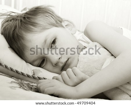 Sad child in bed - stock photo