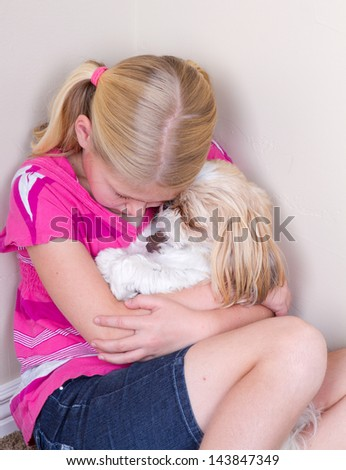 sad child in corner hugging her dog for comfort - stock photo