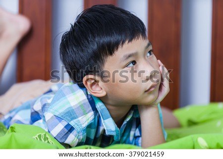 Sad child inside bedroom. Close up handsome asian boy lying on his bed looking sad and lonely. Problem families concept. - stock photo