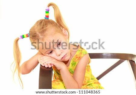 sad child is sitting on a chair - stock photo