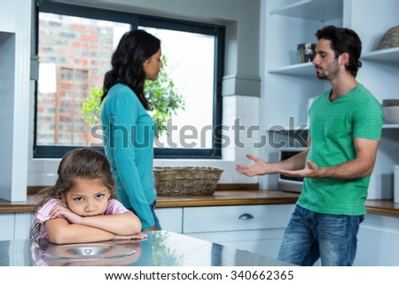 Sad child listening to parents argument in the kitchen - stock photo