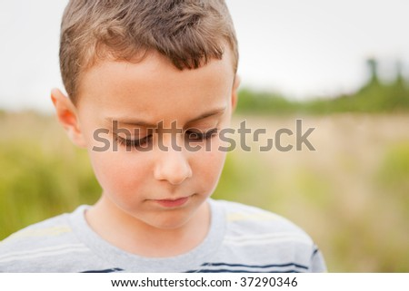 Sad child looking down, outdoors with a forest in background, shallow depth of field - stock photo