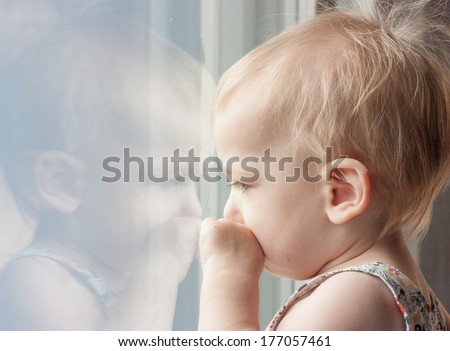 Sad child looking out the window - stock photo