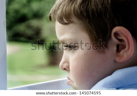 Sad child looking out window on gloomy day - stock photo