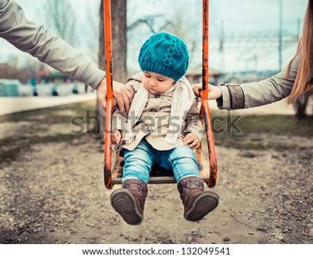 Sad child on a swing, in-between her  divorced parents holding her separately. - stock photo